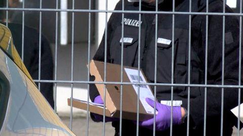 Ein Polizeibeamter hält vor einem Logistikzentrum in Leimen (Rhein-Neckar-Kreis) ein verdächtiges Paket in den Händen