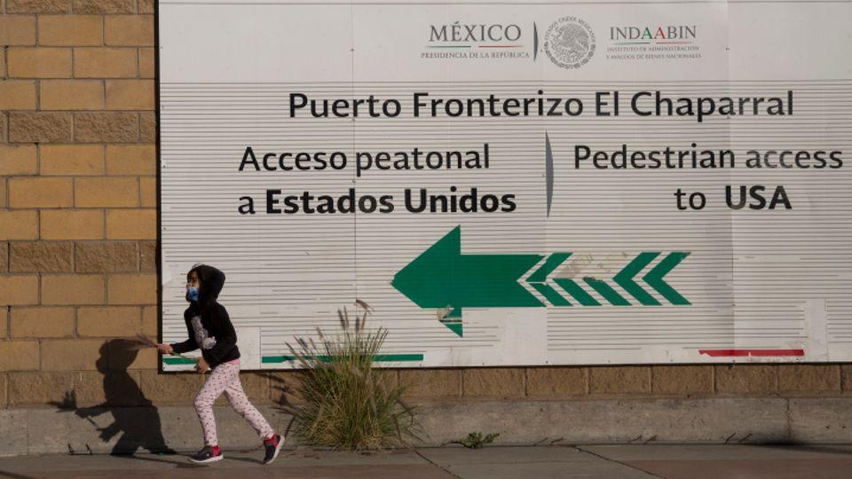 Ein Mädchen spielt, während ihre Eltern am Grenzübergang in Tijuana protestieren