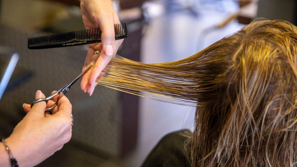 Eine Friseurin schneidet einer Kundin die Haare