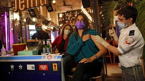 Israel Coronavirus: Eine Frau wird an einem Bar-Tresen gegen das Coronavirus geimpft