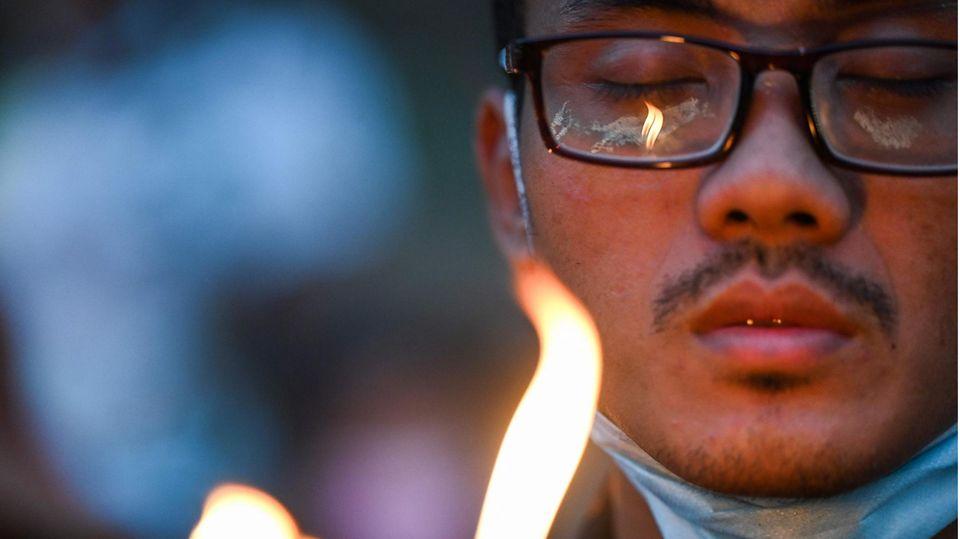 Ein Asiate mit schwarzem Brillengestell hält seine Augen geschlossen, während eine Kerzenflamme sein Gesicht erhellt