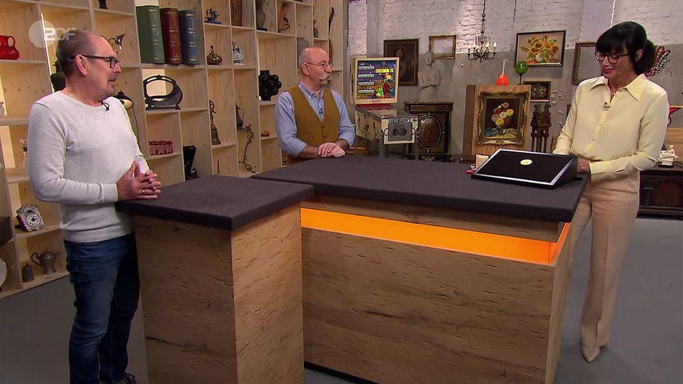 """Gerhard Degenkolb, Moderator Horst Lichter und Expertin Heide Rezepa-Zabel stehen im """"Bares für Rares""""-Studio in Pulheim"""
