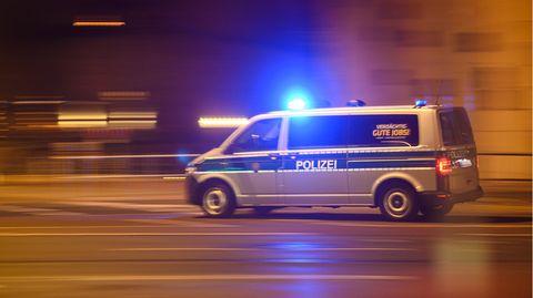 Ein Polizeiwagen mit Blaulicht fährt am Silvesterabend durch die Innenstadt zu einem Einsatz