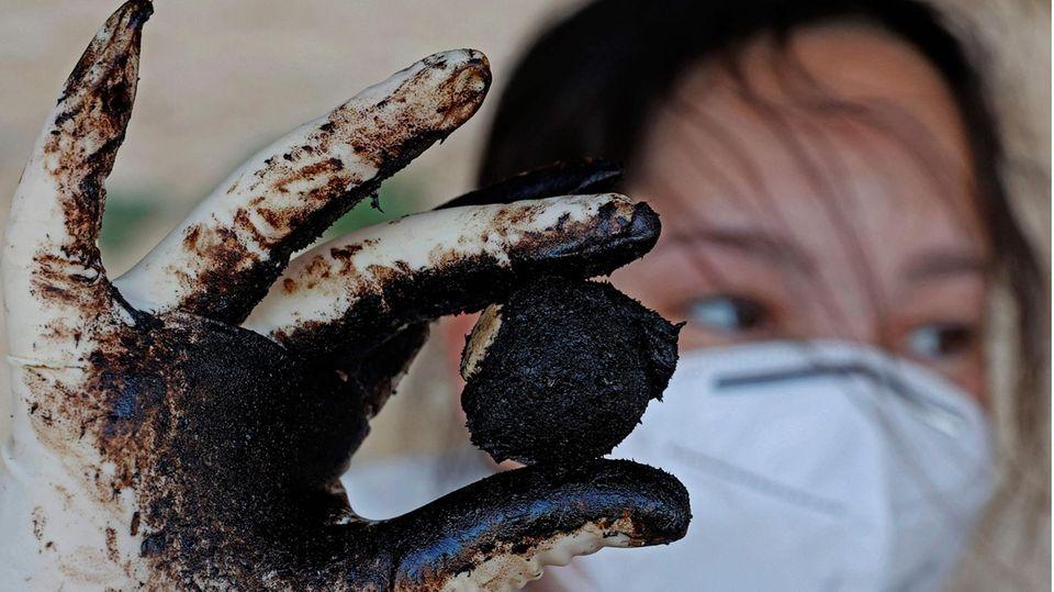 Eine Frau mit langen schwarzen Haaren hält zwischen Daumen und Zeigefinger einen schwarzen Ölklumpen. Sie trägt Gummihandschuhe