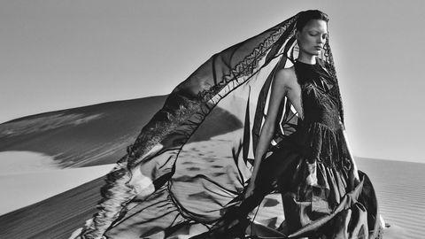 Ein Model trägt ein langes Kleid im Wüstenwind