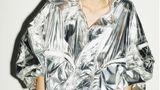 Ein Model in einem silberfarbenen Mantel mot Kapuze