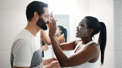 Gesichtscreme für Männer: Eine Frau cremt das Gesicht ihres Partners ein.