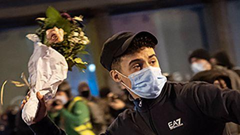Ein Jugendlicher mit schwarzen Locken unter schwarzem Cap trägt eine OP-Maske und wirft einen Blumenstrauß in weißem Papier