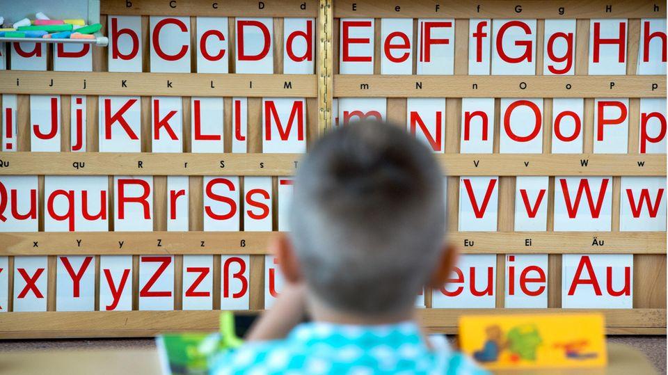 Ein Kind sitztan einem Tisch; im Hintergrund sind Buchstaben zu sehen