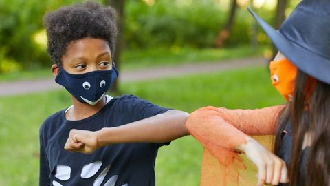 Zwei Kinder mit Masken grüßen sich mit den Ellbogen