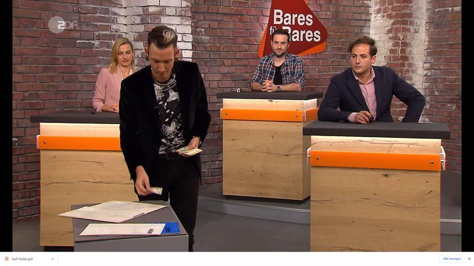 Fabian Kahl steht im Bares für Rares Studio in Pulheim, neben ihm sitzen seine Kollegen