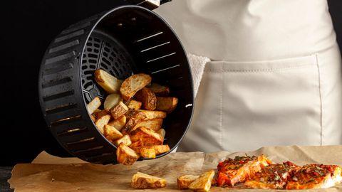 Heißluftfritteuse: Frau kippt fertige Kartoffelspalten aus einem Frittierkorb auf Backpapier
