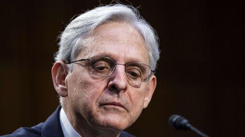 Ein Mann mit grau-weißem Seitenscheitel und Brille sitzt in Anzug vor einem Mikrofon und schaut ernst