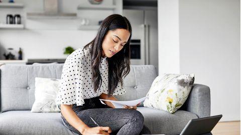 Frau sitzt an Tisch mit Unterlagen und Tablet