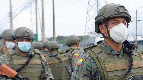 Soldaten mit Helmen und Gewehren marschieren in Ecuador auf ein Gefängnis zu, in dem es einen Aufstand gibt