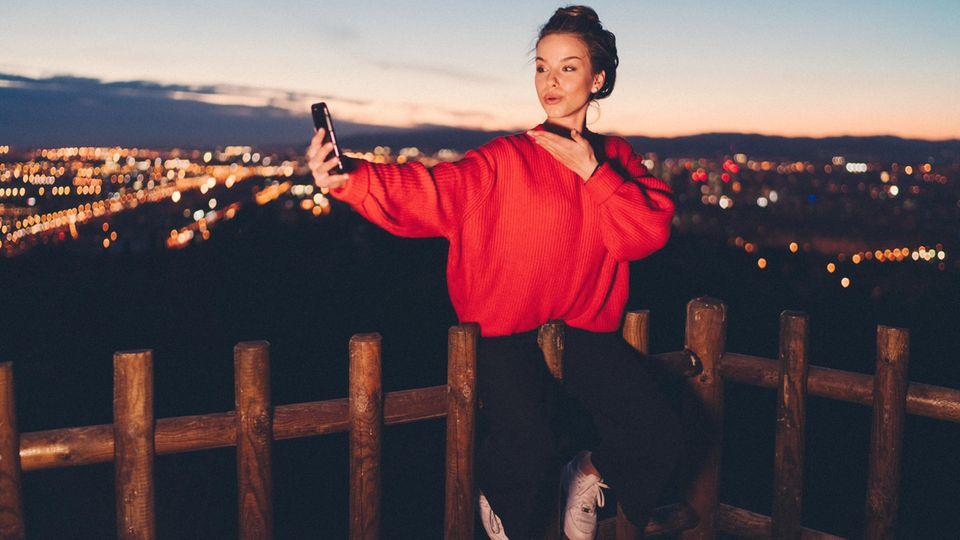 Junge Frau wirft ihrem Handy einen Kussmund zu, hinter ihr ist Barcelona im Dunkeln zu erahnen