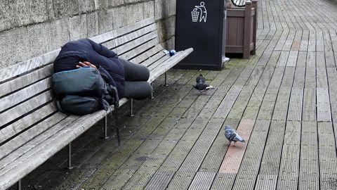 Ein Obdachloser schläft auf einer Bank