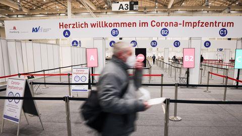 Ein Mann geht durch den Eingang in das Impfzentrum in den Hamburger Messehallen zu seiner Corona-Impfung