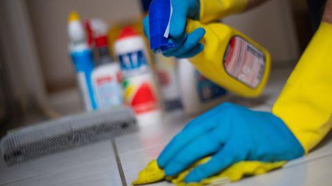 Ein Mann putzt in Gummihandschuhen Fliesenboden in einer Wohnung