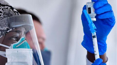 Eine Krankenschwester trägtSchutzkleidung während sie die Dosis einesCorona-Impfstoffes vorbereitet