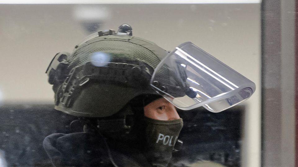 Ein Polizist in grüner Uniform und Sturmhaube unter dem Helm ist mit hochgeklapptem Visier im Profil zu sehen