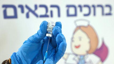 Zwei Hände in blauen Gummihandschuhen ziehen den Corona-Impfstoff von Biontech aus einer Ampulle auf eine Spritze