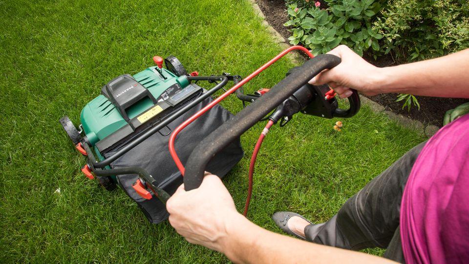 Rasen vertikutieren: Frau schiebt einen Elektro-Vertikutierer über ihren Rasen