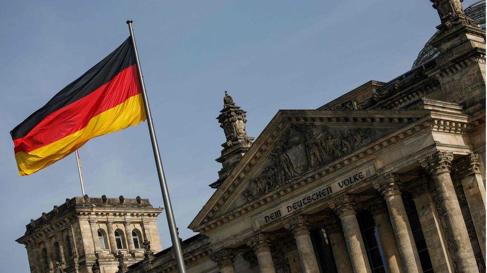 Eine Deutschland-Fahne weht vor dem Bundestagsgebäude in Berlin