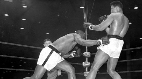 """25. Februar 1964:Der 22-jährige US-Schwergewichtler Cassius Clay (re.) – später Muhammad Ali – versucht einem Schlag seines Kontrahenten Charles """"Sonny"""" Liston auszuweichen. Der Kampf am 25. Februar 1964 in Miami Beach in Florida endet mit einer Sensation: Der sieben Jahre ältere Liston verliert in der 7. Runde durch technischen K.o. seinen Titel an den Herausforderer aus Kentucky. Eine Verletzung der linken Schulter Listons ist für Ringarzt Dr. Robbins Anlass, in der Pause zur siebten Runde den Kampf abzubrechen. Clay rief dann den Zuschauerinnen und Zuschauern und Reportern jenen Satz zu, der zu seinem Markenzeichen werden sollte:""""I am the greatest!""""– """"Ich bin der Größte!"""""""