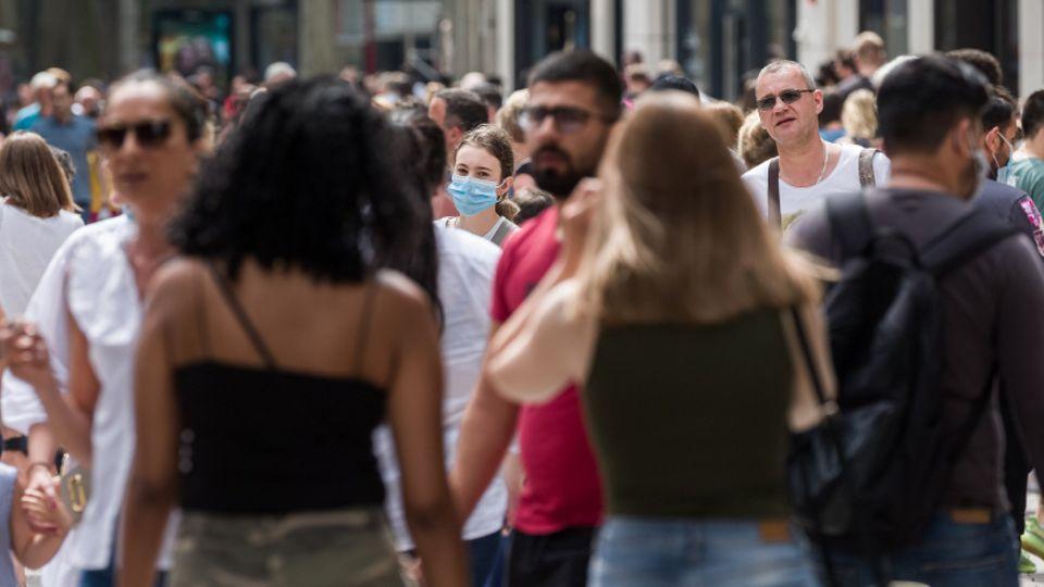 Passanten tummeln sich in einer Einkaufsstraße.