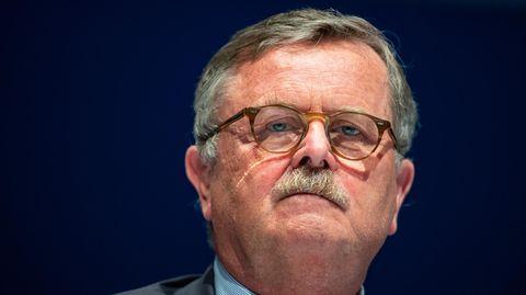 Ein Mann mit angegrautem Seitenscheitel, grauen Schläfen und Schnauzbart sowie einer Hornbrille schaut ernst