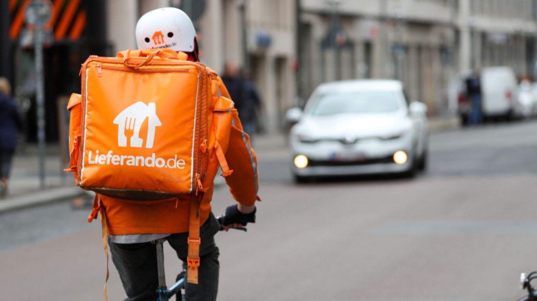 Ein Lieferando-Fahrer in orangefarbener Jacke fährt auf dem Fahrrad