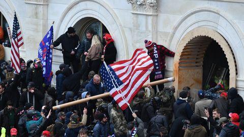 Eine Menschenmenge mit US- und Trump-Flaggen drängt bewaffnet gegen ein weißes Gebäude vor