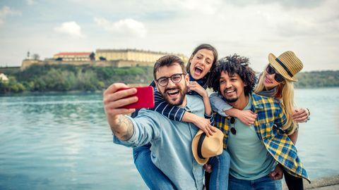 Eine Gruppe junger Menschen macht ein Selfie mit einem Handy mit guter Kamera unter 300 Euro.
