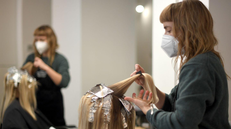 Friseurin beim Haarefärben einer Kundin mit Mundschutz