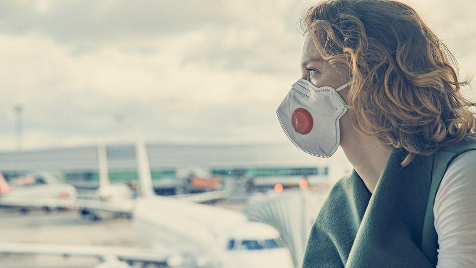 Frau mit Maske blickt sehnsüchtig aus dem Fenster auf das Rollfeld eines Flughafens.