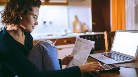 Kreditvergleich: Frau sitzt mit Taschenrechner und Laptop an einem Tisch