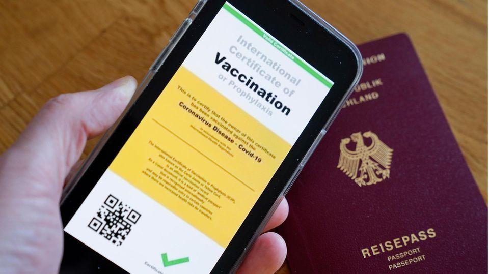 Symbolbild eines möglichen digitalen Impfpasses der Europäischen Union und eines deutschen Reisepasses