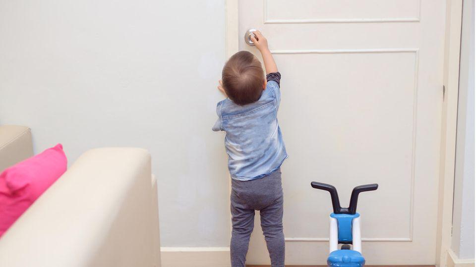 Ein Kind versucht, eine Zimmertür zu öffnen
