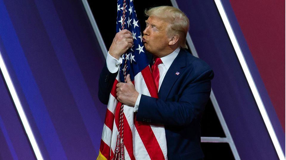 Donald Trump küsst und umarmt eine amerikanische Flagge