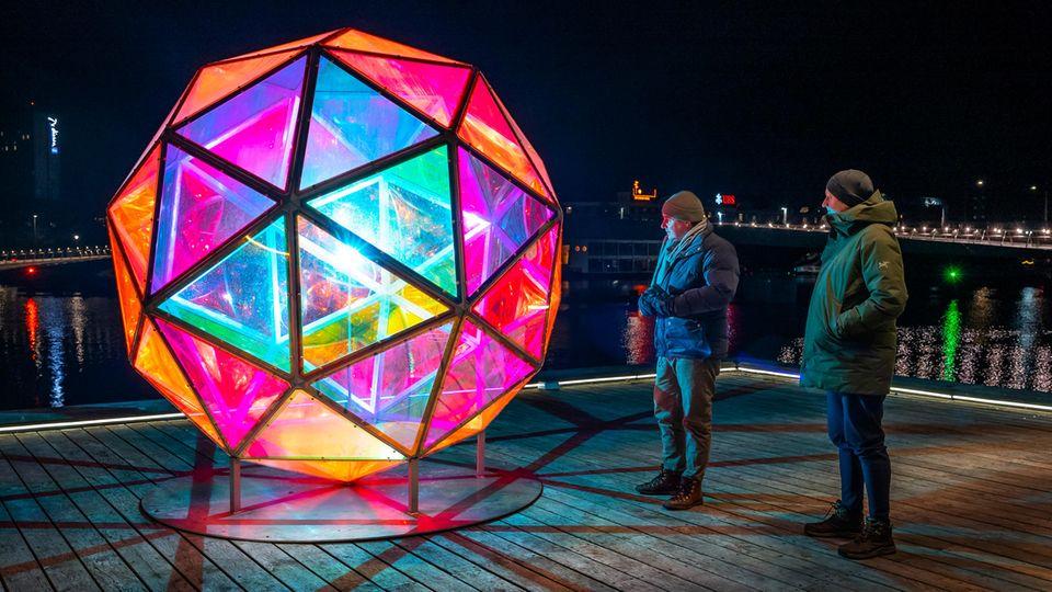 Zwei Männer stehen in Winterkleidung vor einer von innen beleuchteten Kugel aus bunten Glas-Dreiecken