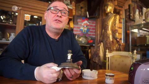 """Walter Lehnertz sitzt in seinem Geschäft """"Waldi's Eifel Antik"""" in Kall und poliert den Silberdeckel"""