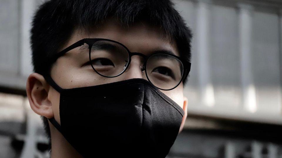 Ein Asiate trägt eine Brille mit schwarzem Gestell und einen schwarzen Mund-Nasen-Schutz