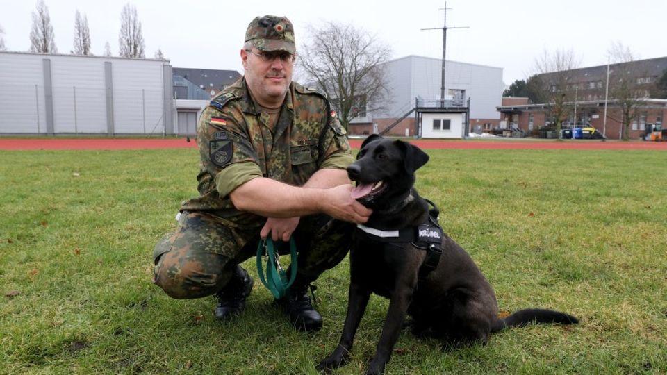Ein Bundeswehr-Offizier hält einen Therapiehund an der Leine.