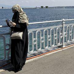 Eine Frau mit Niqap steht am Genfer See und liest in einem Stadtplan.
