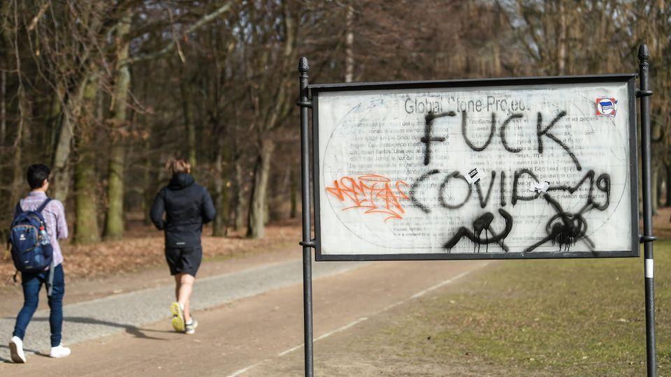 """Jogger laufen im Berliner Tiergarten an einem """"Fuck Covid""""  Schriftzug vorbei"""