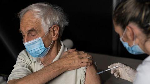 Eine Krankenschwester sticht einem älteren, weißhaarigen Mann eine Spritze in den linken Oberarm. Beide tragen OP-Masken