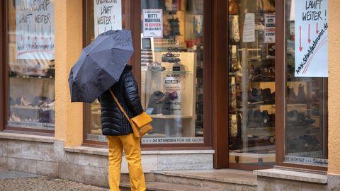 Thüringen, Gotha: Eine Frau steht vor einem geschlossenen Schuhgeschäft und betrachtet die Schuhmodelle