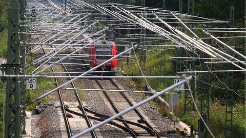 Eine Diesellok fährt auf der mit neuen Masten und Stromleitungen versehenen Bahnstrecke München-Lindau