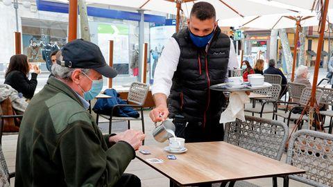 Spanien, Palma: Ein Kellner serviert einem Kunden einen Kaffee